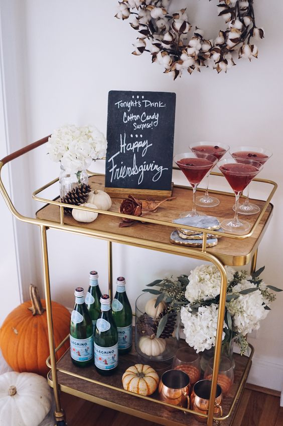 pumpkins, pinecones, white hydrangeas, a chalkboard sign and a cotton wreath over the cart