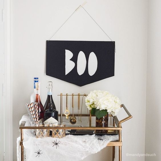 simple modern styling with a black sign, fake spiderweb and spiders and white hydrangeas