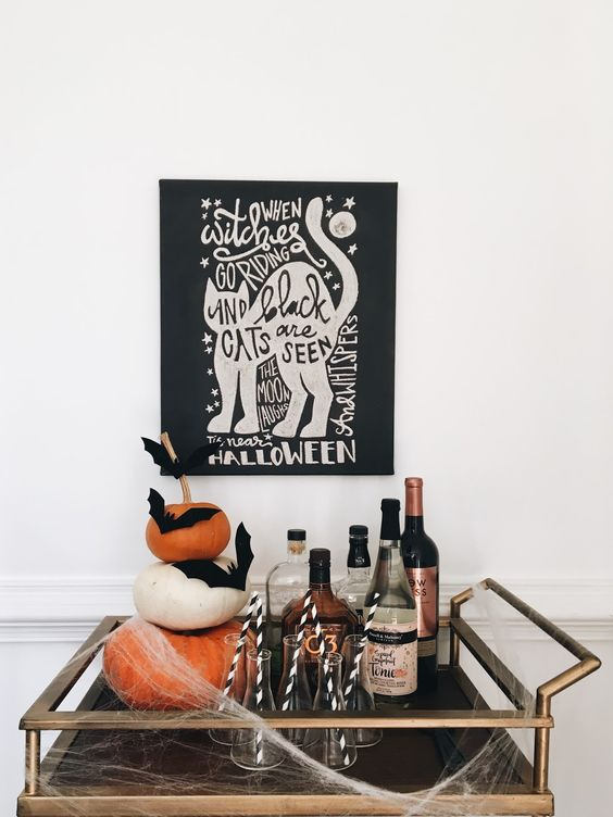 simple styling with a stack of pumpkins and black bats plus some fake spiderweb and a sign