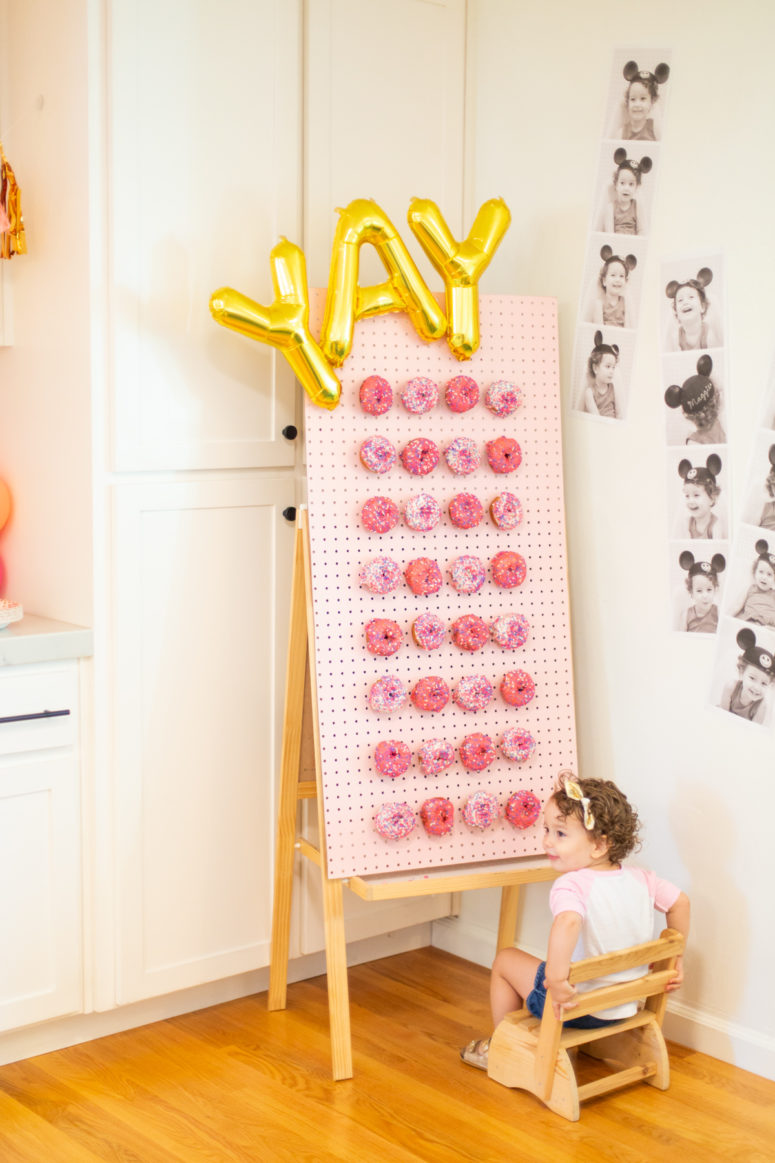 DIY donut wall with letter balloons and pink donuts (via lovelyindeed.com)