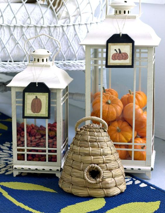 white lanterns with tags filled with real berries and fake orange pumpkins are amazing for fall decor