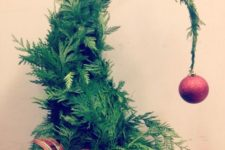 02 a Grinch-inspired fern Christmas tree with a plaid bow and a red glitter ornament on top