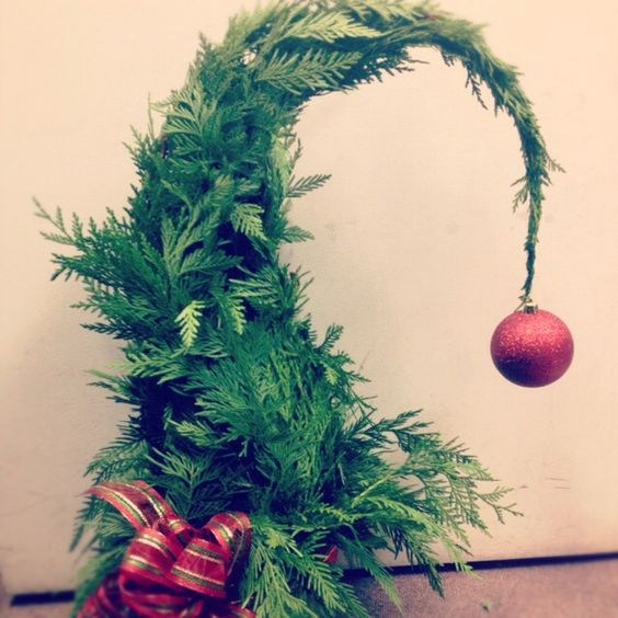 a Grinch-inspired fern Christmas tree with a plaid bow and a red glitter ornament on top