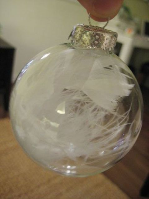a clear glass ornament filled with white feathers is a modern and bold idea for Christmas