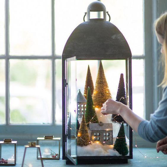 an oversized lantern with cotton, cardboard houses, fake trees and LEDs feels very wintry-like