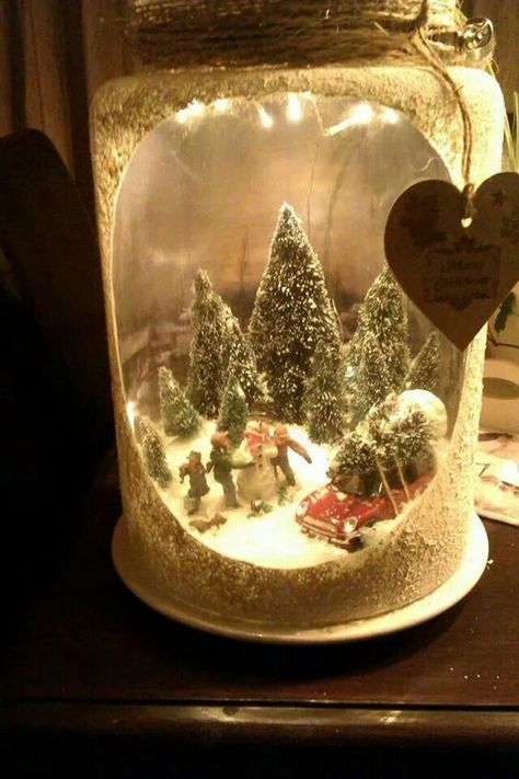 a Christmas lantern with a winter scene, people, snowmen, a car and lots of trees