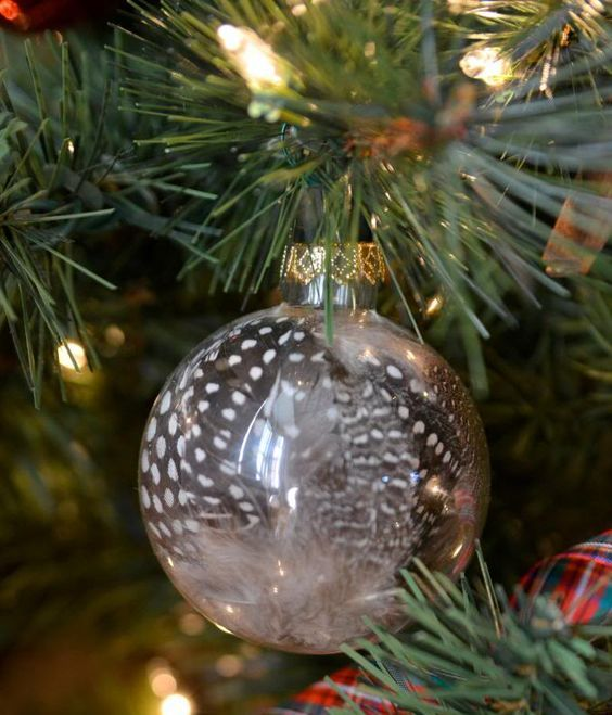 a modern holiday ornament of clear glass filled with guinea feathers is a fun idea you can easily DIY
