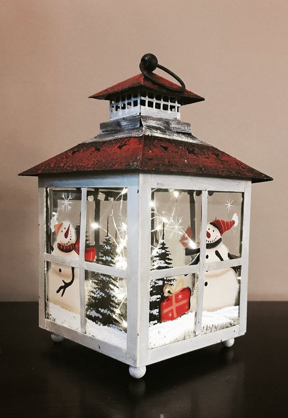 a Christmas lantern with a winter scene, snowmen, trees, LEDs and fake snow is adorable