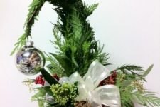05 a Grinch Christmas tree in a red pot, with fresh greenery, a whte bow and a single silver ornament
