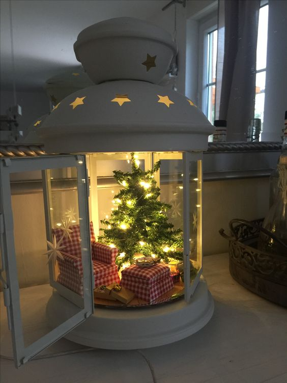 a large lantern with a wintry look, a plaid chair with an ottoman and a tree with lights