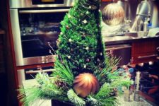 06 a Grinch tabletop Christmas tree decorated with two large ornaments, pinecones and beads is a whimsy decoration