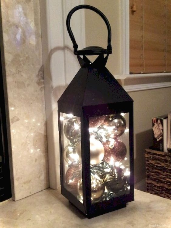 a black lantern filled with ornaments and lights is a very easy to realize idea