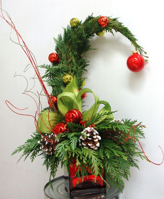 a bright Grinch-inspired Christmas tree of ferns, yellow and red ornaments, snowy pinecones and plaid