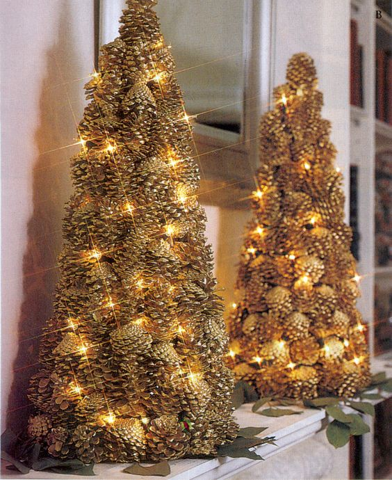 a couple of gilded pinecone Christmas trees decorated with lights look very festive and interesting