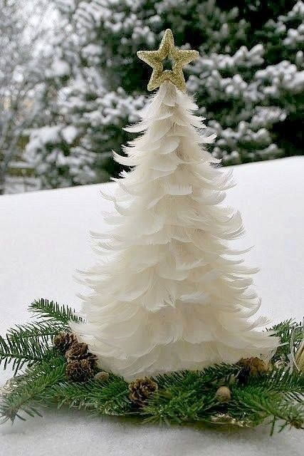 a cute feather Christmas tree topped with a gold glitter star and on evergreens and pinecones