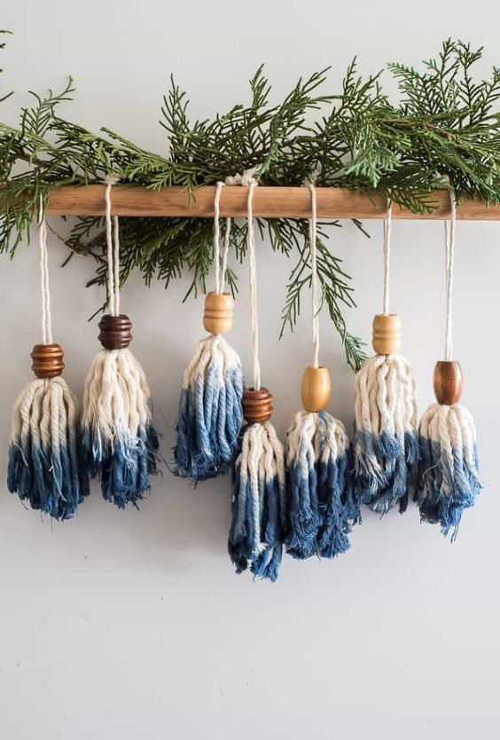 blue dipped tassel and bead Christmas ornaments hung on a wooden stick with fresh evergreens