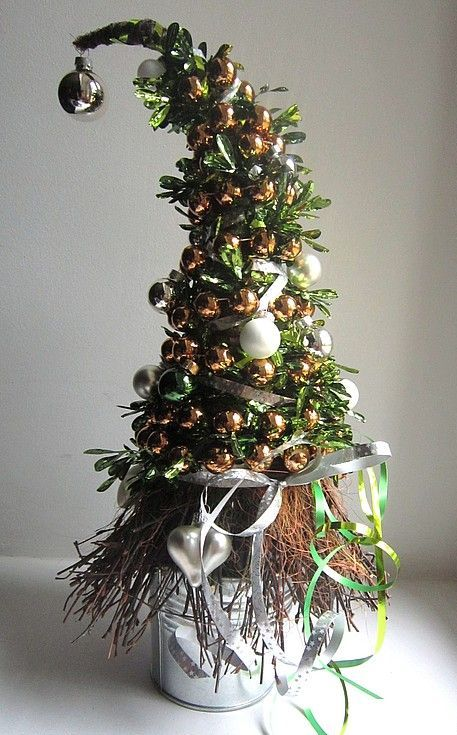 a bright tabletop Christmas tree with gold, white and emerald ornaments in a tin can