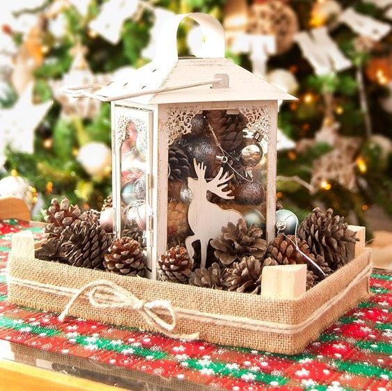 a chic white Christmas lantern with ornaments, pinecones and a deer silhouette