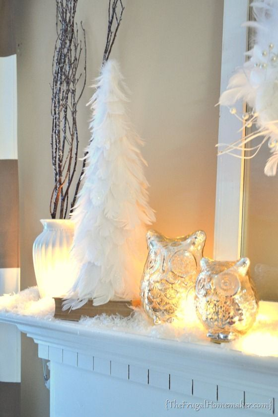 a cute winter mantel with owls, lights, cotton and a feather Christmas tree in pure white