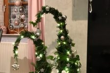 09 a duo of Grinch-inspired Christmas trees with lights, silver ornaments and with vines