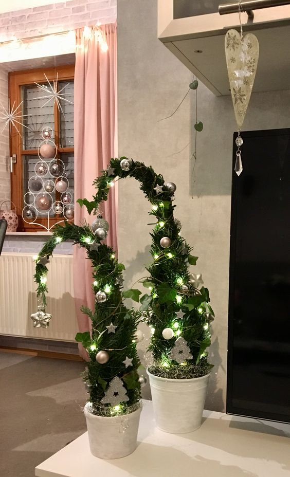 a duo of Grinch-inspired Christmas trees with lights, silver ornaments and with vines