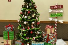 10 a Grinch curved Christmas tree decorated with lights, ornaments, pompom garlands and bold gifts under the tree