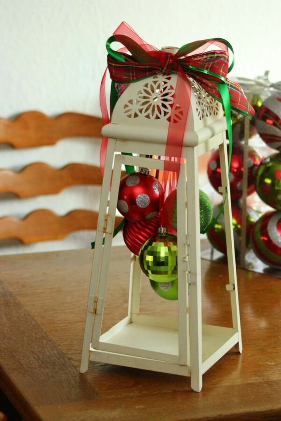 a lantern with no glass with some bright ornaments hanging inside and ribbon bows on top
