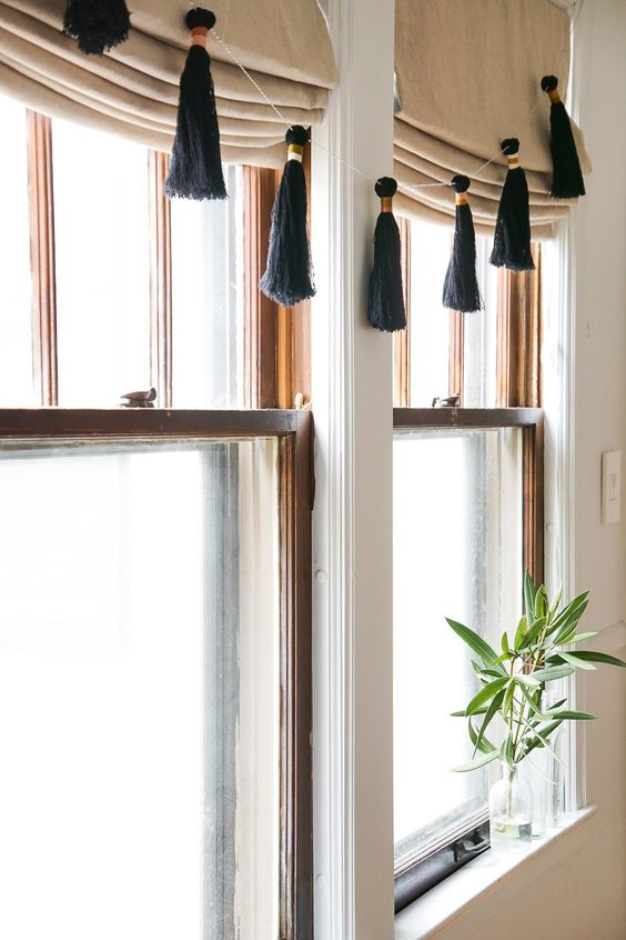 an elegant black and copper holiday tassel garland will spruce up your neutral window treatments