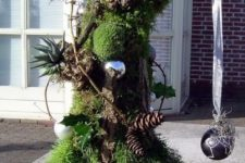 11 a Grinch-inspired Christmas tree of moss, a stump, branches, with evergreens, pinecones, ornaments and succulents for outdoors
