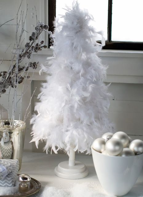 a pure white feather Christmas mini tree and matching pearly ornaments in a bowl next to it