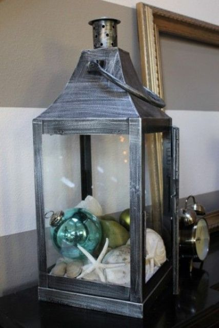 a shabby chic lantern styled for beach Christmas, with ornaments and shells plus starfish