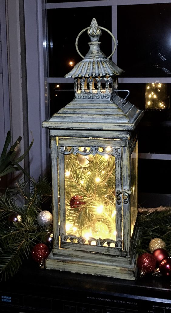 a shabby chic lantern with evergreens, ornaments and lights is a very festive-like idea