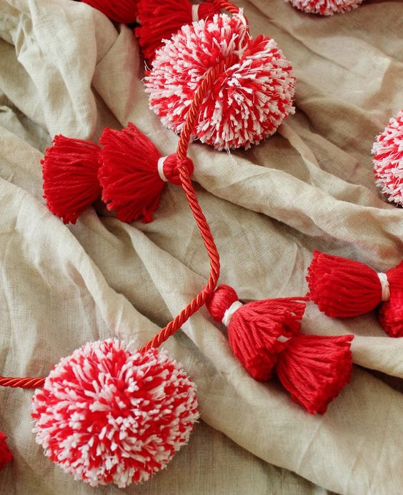 color up your holidays with a red and white tassel and pompom garland made for almost nothing