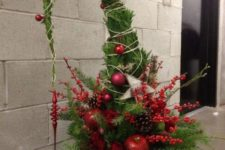 13 a lush and colorful Grinch Christmas tree with red ornaments, beads, fake berries, fruit and pinecones in a pot