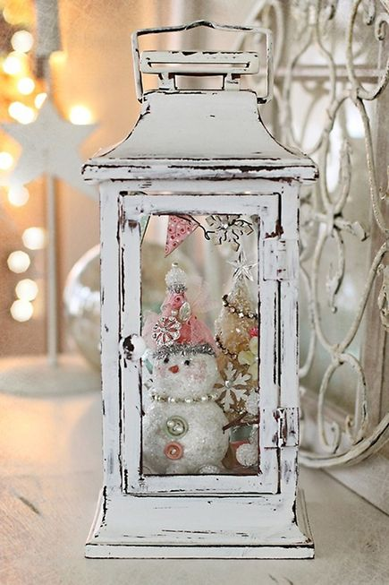 a shabby chic white lantern with vintage Christmas ornaments, a tree and a snowman