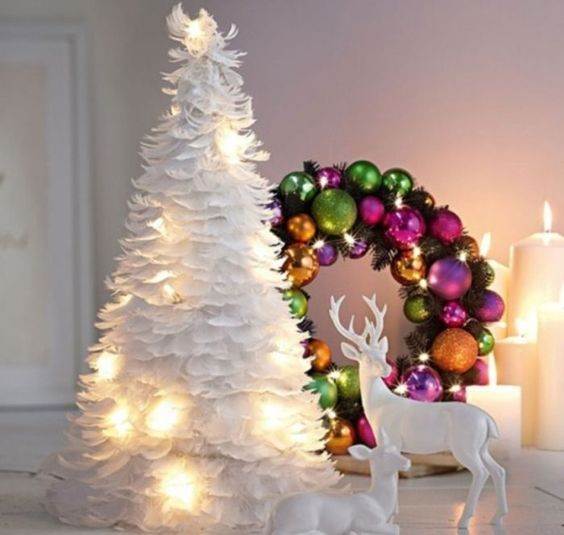 a white feather Christmas tree with lights and a colorful ornament wreath with lights are a great combo