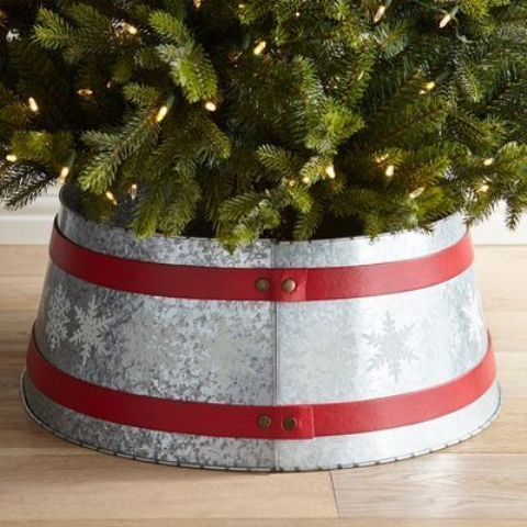 a galvanized metal tree collar with snowflakes and red ribbons on the whole diameter