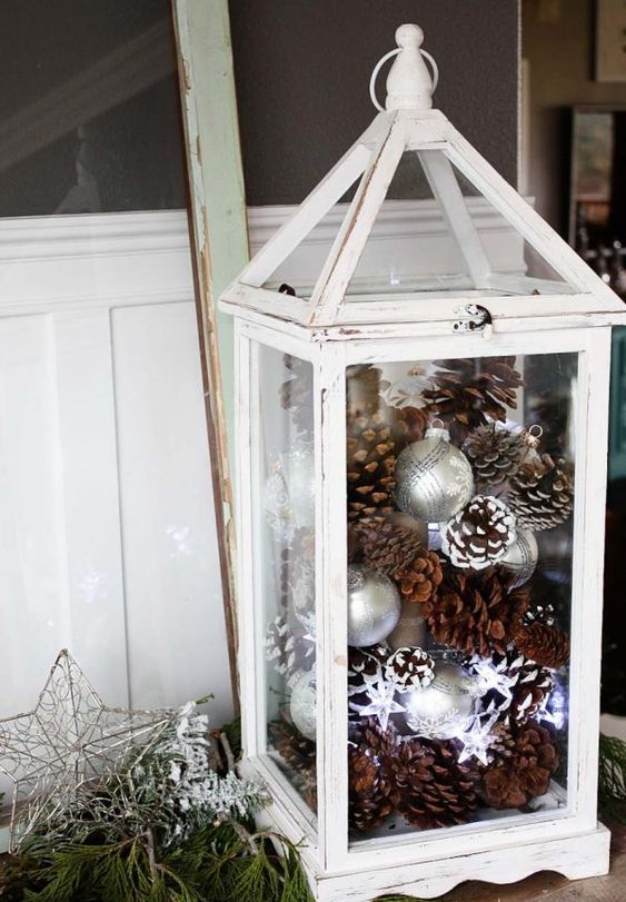 a white lantern with pinecones, ornaments and star-shaped lights for winter holidays