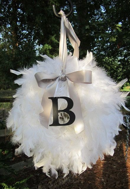 a lit up Christmas feather wreath decorated with a large bow and a monogram is amazing for holidays and looks so heavenly
