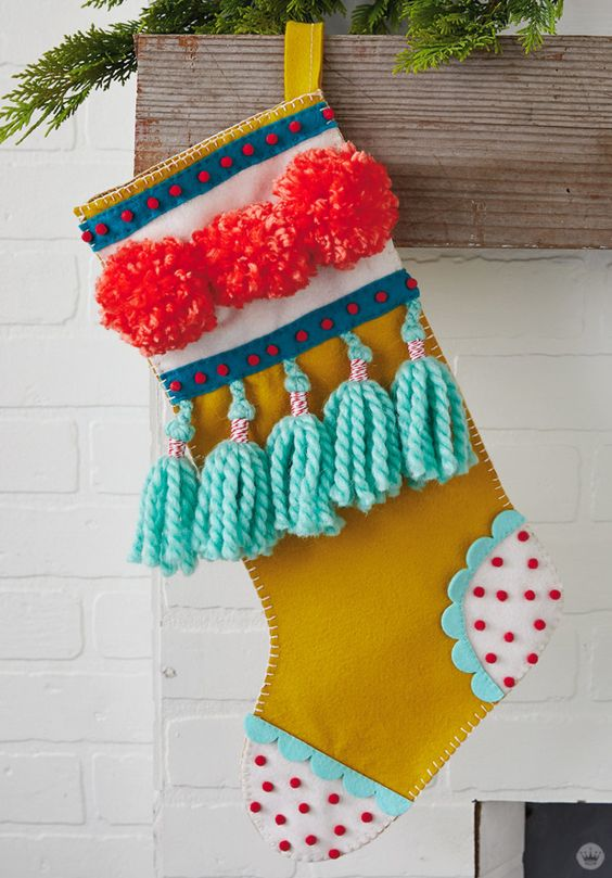a super colorful Christmas stocking with pompoms and tassels is a bright decor idea