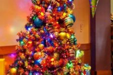 15 a super colorful and large Grinch Christmas tree decorated with lights and bright ornaments of all colors