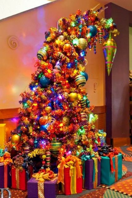 a super colorful and large Grinch Christmas tree decorated with lights and bright ornaments of all colors