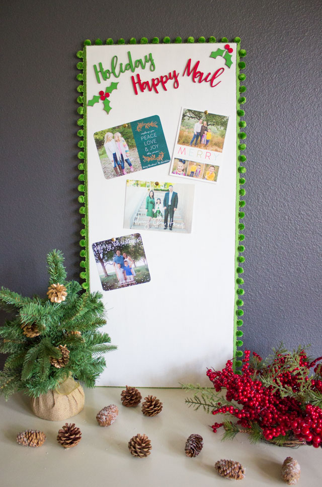 DIy cork board with pompom trim Christmas card display (via www.designimprovised.com)