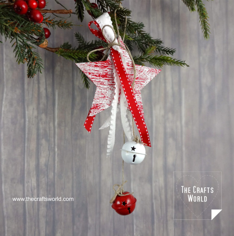 DIY Christmas ornament of a wooden star and jingle bells (via thecraftsworld.com)