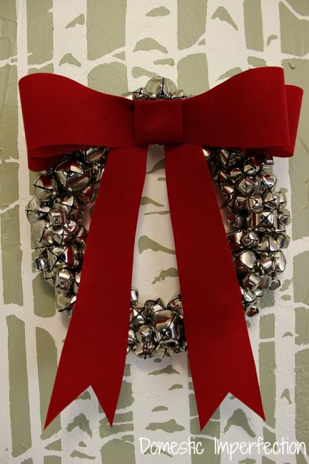 DIY large jingle bell wreath with a large red bow (via www.domesticimperfection.com)