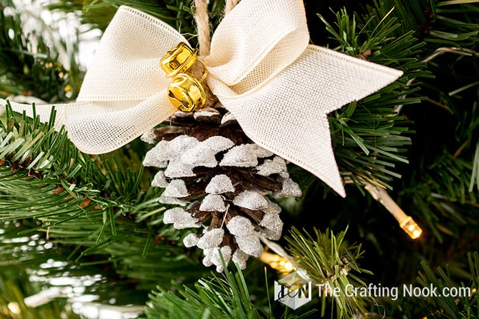 DIY cute snowy pinecone ornaments with jingle bells and ribbon bows (via thecraftingnook.com)