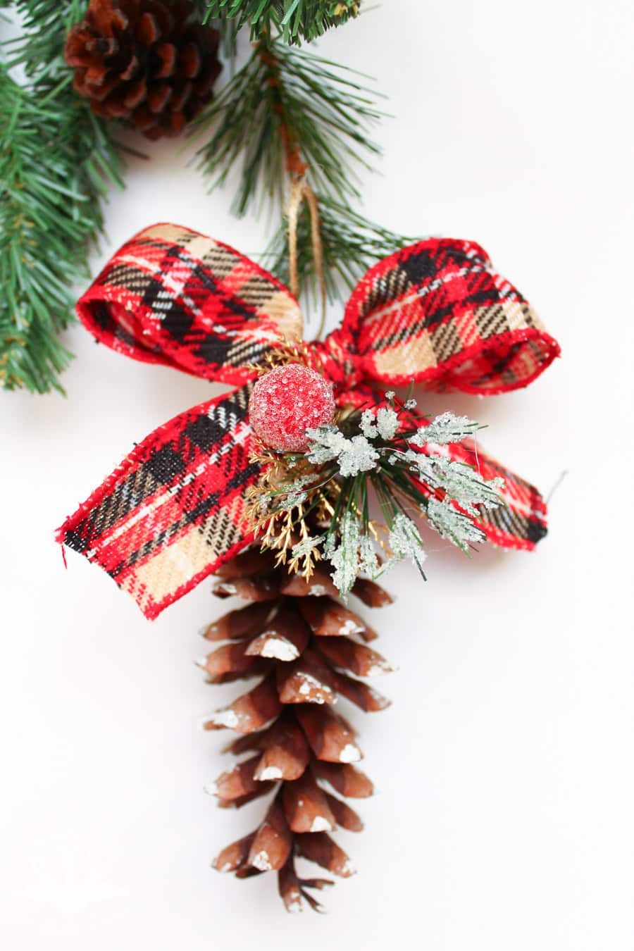 DIY pinecone ornaments with plaid ribbon bows and fake greenery and berries