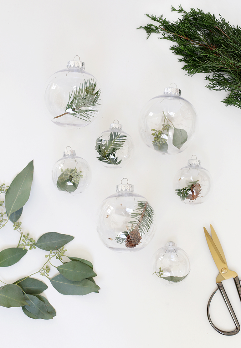 DIY clear Christmas ornaments filled with greenery and little pinecones (via themerrythought.com)