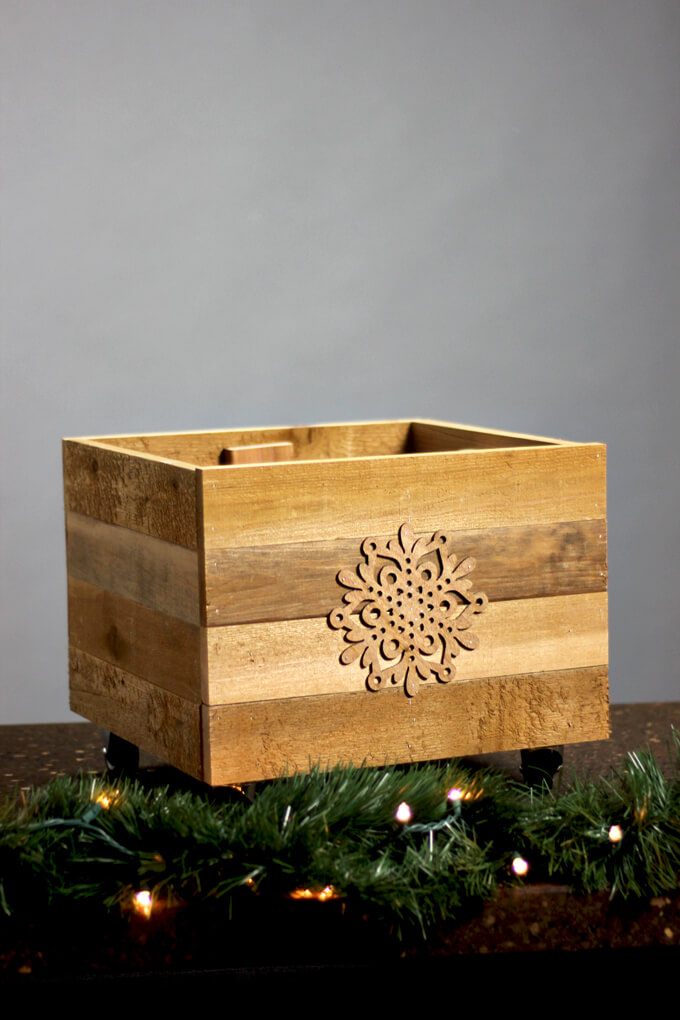 DIY rustic Christmas tree crate on casters decorated with a snowflake