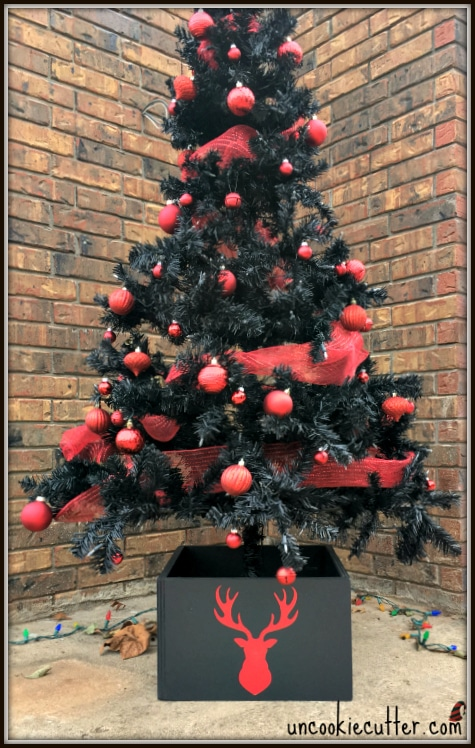 DIY black Christmas tree stand box with a red deer silhouette (via www.uncookiecutter.com)